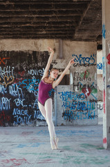 Young ballerina dancing in old building