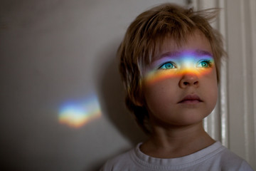 Little girl with a rainbow of light across her eyes