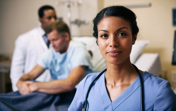 Hospital Confident Nurse With Doctor Checking Patient In Background