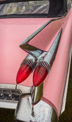 Tail light of a pink classic american car from the fifties