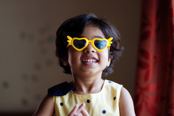Little girl having fun wearing heart shaped sunglasses
