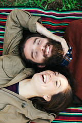 Overhead of a couple laughing resting on a striped blanket in the park