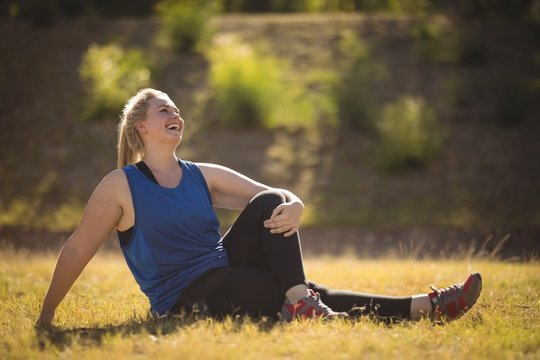 Happy woman relaxing on grass during obstacle course