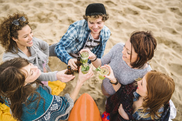 Group of friends toasting on the beach