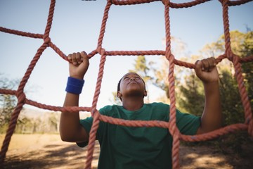 Determined boy climbing a net during obstacle course