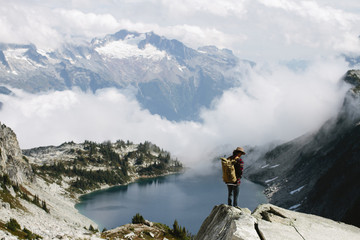 Young man stands on cliff looking out at lake