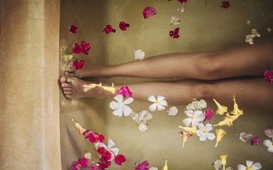 Legs of a Woman Relaxing in a Bathtub Full of Flowers