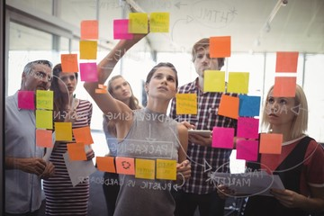 Business people planning with adhesive notes in creative office