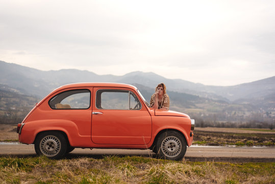 Young woman standing next to the vintage car in the countryside