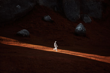 A lone astronaut descends the side of a mountain