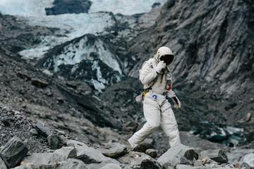 Astronaut travels across rigid landscape