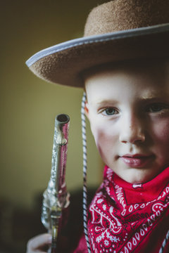 Young boy dressed up like a cowboy with hat, gun and bandana