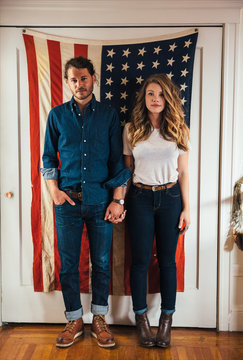 Portrait of couple standing in front of American flag at home