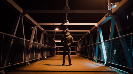 Backside view of a man standing on the bridge