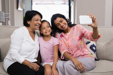 Happy multi-generation family taking selfie together at home