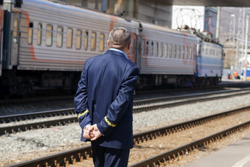 The train conductor awaits his arrival on the platform