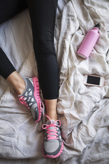 Woman in Running Tights and Trainers Lying in Bed after the Workout