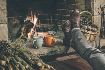 Man relaxing beside a fireplace in her comfortable home