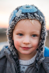 Potrait of a young blonde little boy with funny winter cap