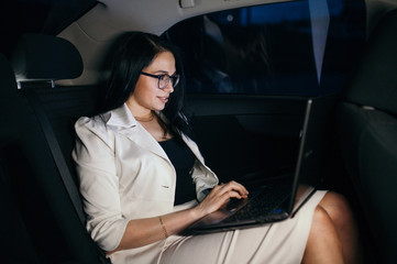 Young beautiful successful businesswoman sitting in the luxurious car and using laptop.
