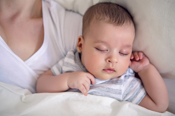 baby sleeps next to mom in the big parental bed