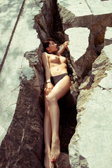 Fashion Photo of Sexual girl topless at old stone quarry. Summer holidays. Vintage colors.