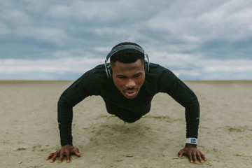 Young Black Guy Doing Push Ups on the Beach