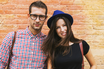 Portrait of young beautiful couple in front brick wall