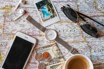 Close-up of smartphone, watch, sunglasses, money, coffee on the map