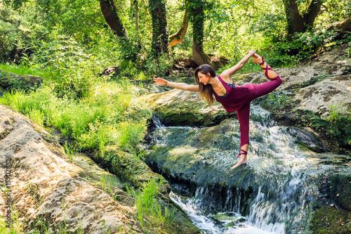 Jolie jeune femme sportive pratiquant le yoga dans la nature  posture du  danseur - Natarajasana a4cf3980723
