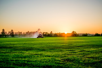 water pump at sunset in a big green field Europe