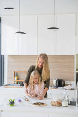 Portrait of adorable little girl and her mother making pizza together at home