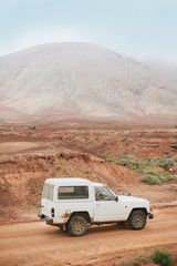 Couple in Adventure with Car in the Middle of the Desert Area
