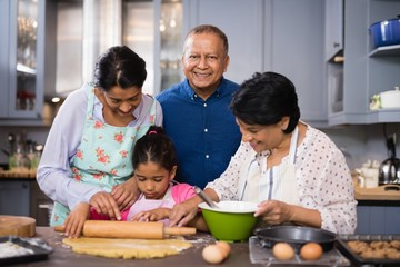 Portrait of smiling man with family preparing food in kitchen