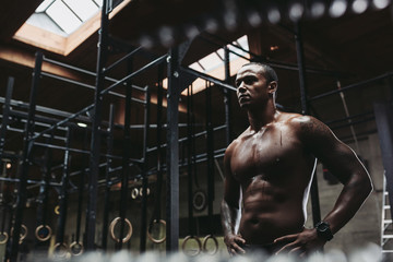 Young, fit black man recovering after training hard in fitness gym