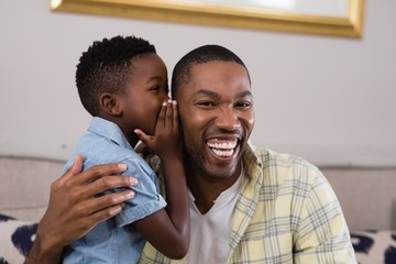 Boy whispering father on sofa at home