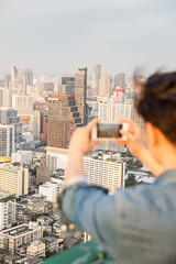 Young man taking picture with smartphone on city view during vacation