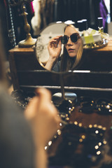 Young woman trying sunglasses in a vintage store