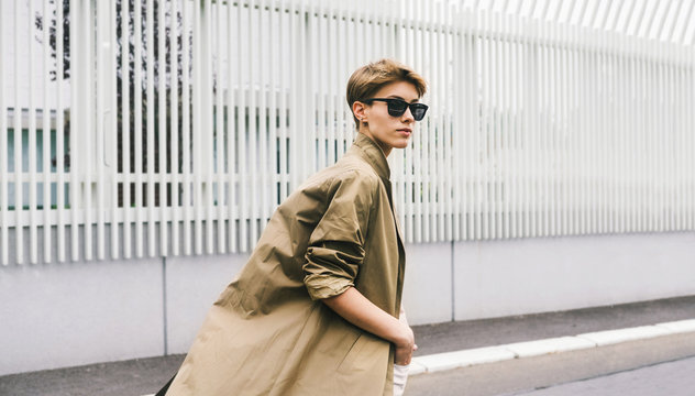 Stylish short hair young woman in coat walking down the street