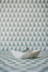 Origami boat on wallpaper background