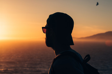 A young man watches the sunset over the Pacific Ocean