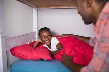 Father talking to daughter lying on bed at home