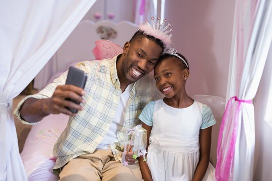 Father and daughter taking selfie while sitting on bed at home