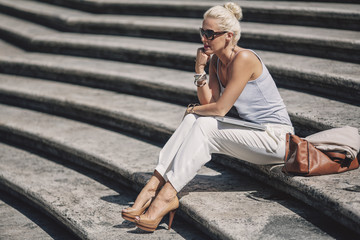 Beautiful Blonde Woman Sitting on Stairs Outdoors