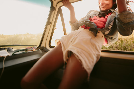Adventurous young woman hangs outside moving vehicle