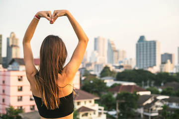 Young woman making a heart sign with her body