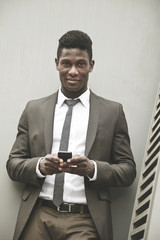 African young businessman looking at camera with a smartphone