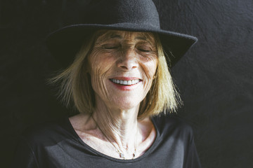 Portrait of smiling senior woman with a black hat