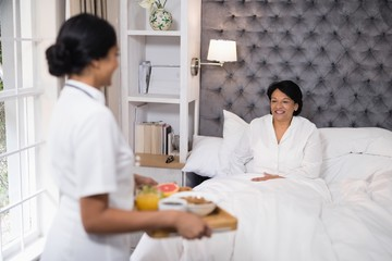 Side view of nurse serving breakfast to patient