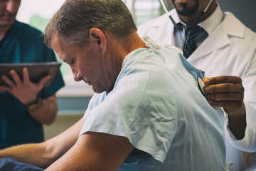 Hospital Doctor Listents To Patient's Lungs During Exam